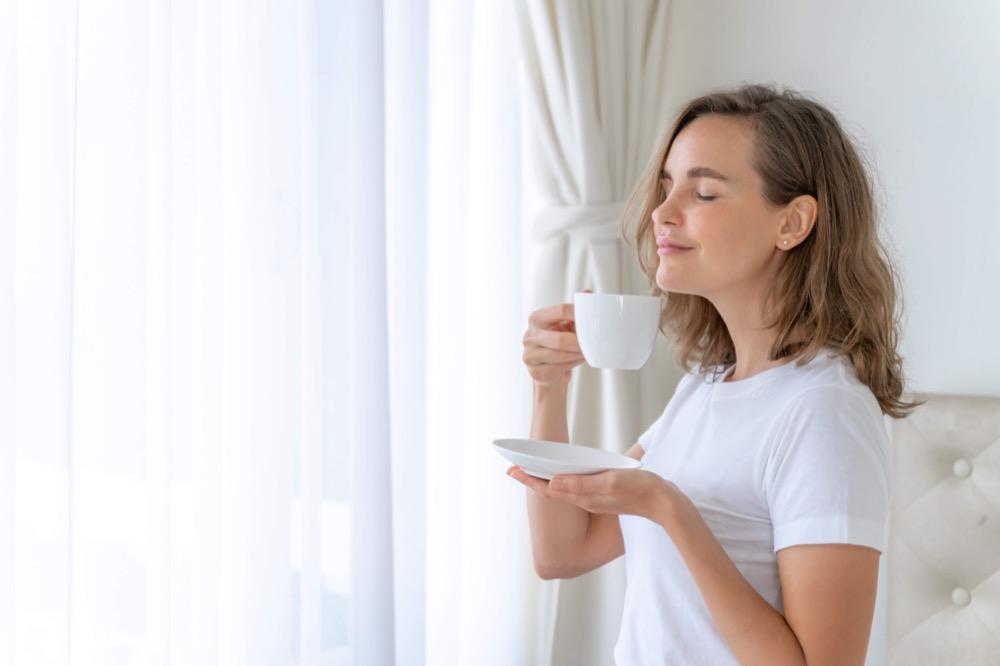 femme buvant du thé devant sa fenêtre